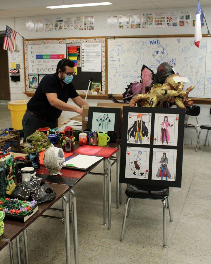 Art teacher Luis Trejo-Fuentez does last minute adjustments to his student's art pieces before taking them to the Ellen Noel Art Museum for the High School Art Exhibit.